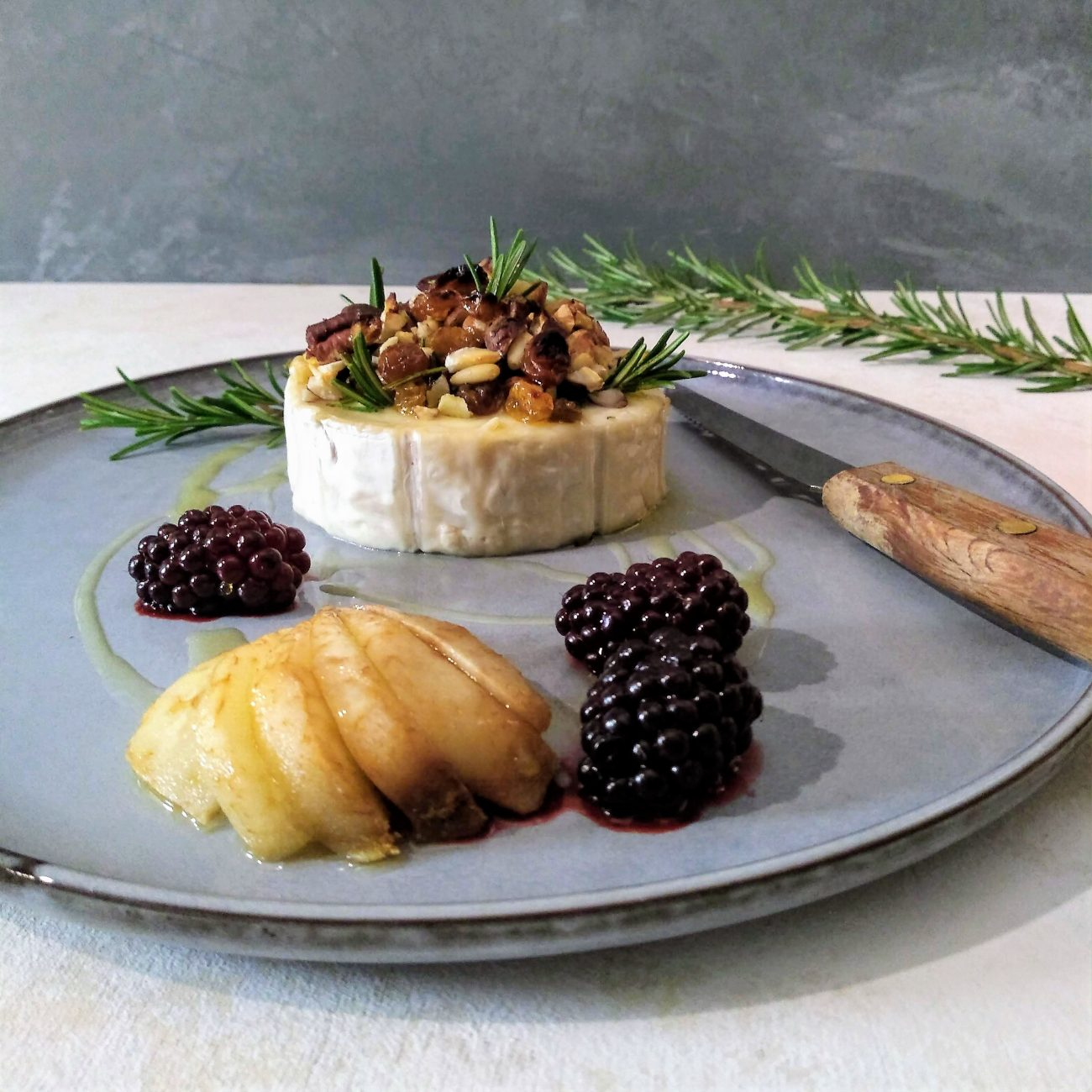 Warme geitenkaas met noten, honing, peer en bramen
