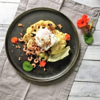 Bloemkoolsteak met grijze garnalen, gepocheerd ei en walnoot crumble